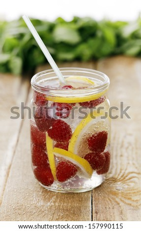 A jar full of cold drink with lemon and raspberries over a wooden surface - stock photo