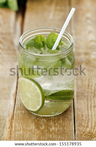 A jar full of mojito with ice and a straw - stock photo