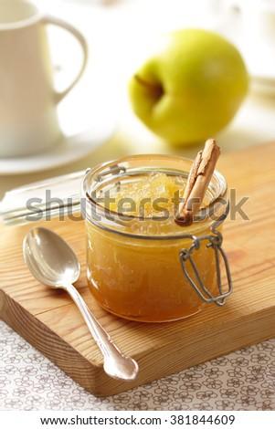 A jar of apple jam with cinnamon on a breakfast table. - stock photo