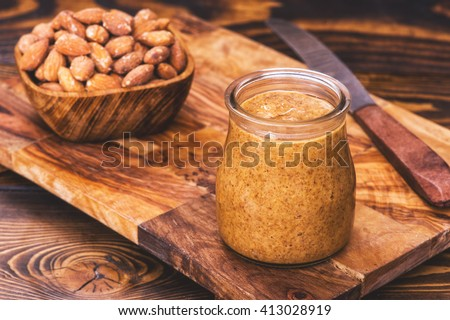 A jar of homemade raw organic almond butter with a wood bowl of fresh salty almonds and knife  on the side on the wood board on the brown old rustic wooden background - stock photo