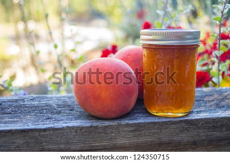 A jar of peach jelly with ripe peaches - stock photo