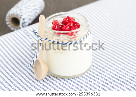A jar of  plain yogurt with oats and berries on a wooden table with striped table cloth. Healthy breakfast choice. - stock photo