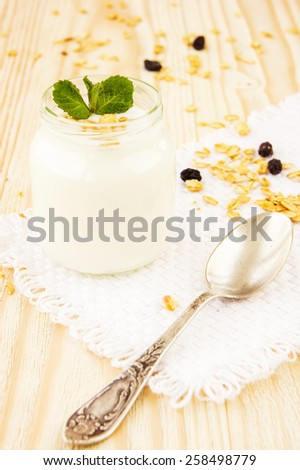 A jar of yogurt with honey glazed oatmeal, nut and coconut chips granola on wooden background - stock photo