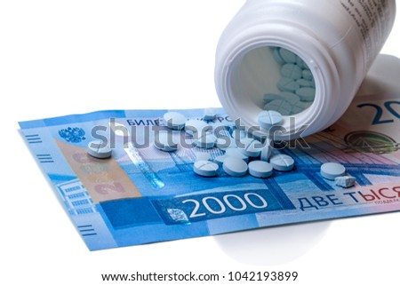 A jar with blue pills and a 2000 rubles banknote on a white background