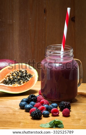 A jar with fresh purple fruit juice next to raw blueberries, blackberries, raspberries, a papaya fruit, and some mint leafs on a rustic wooden table. - stock photo