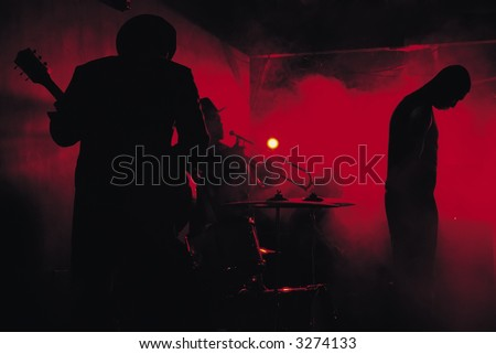 A jazz band shot in silhouette while performing in a club - stock photo