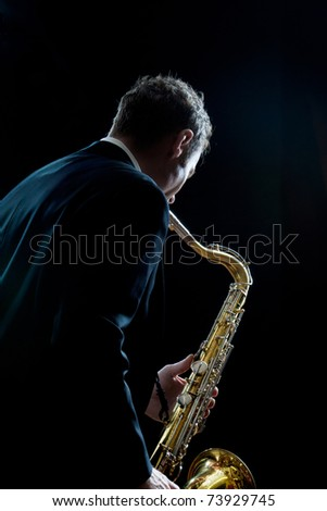 A jazz saxophone player facing the audience as he plays - stock photo