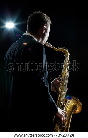 A jazz saxophone player facing the audience as he plays in a club - intentional flare - stock photo
