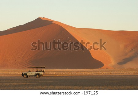 A jeep on a trail near a sand dune, Namibia, Africa - stock photo