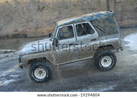A jeep speeding along a mountain river. Intentional motion blur to emphasize speed. the Caucasus - stock photo
