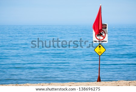 A jellyfish or marine stinger warning sign and red flag at a tropical Australian beach. - stock photo