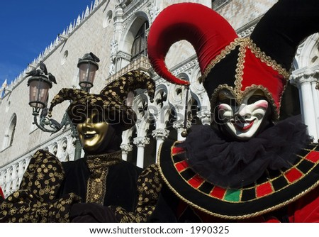 a jester and a joker clown around in st marks square and welcome you to Carnivale, in Venice,Italy,the mardi gras of Europe. - stock photo