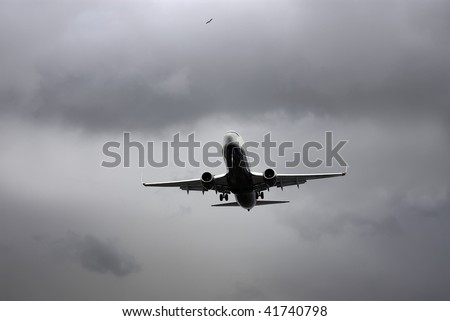 A Jet carrier on final approach in stormy sky.A seagull flying above.