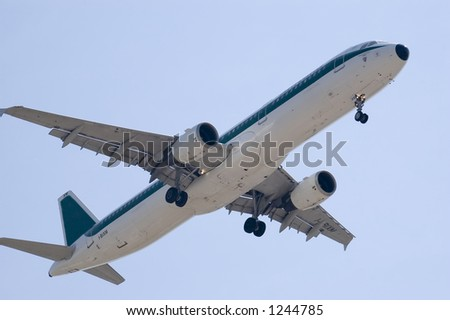 A jet landing (Airbus A300) over a blue sky - stock photo