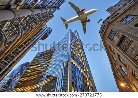 A jet plane flying low over Three different kind of architecture with commercial office buildings exterior. Evening view at bottom skyscrapers. - stock photo