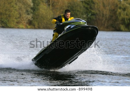 A jet ski rider and his personal watercraft leaping out of the water - stock photo