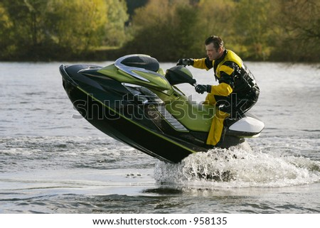 A jet skier gets his personal water craft out of the water - stock photo