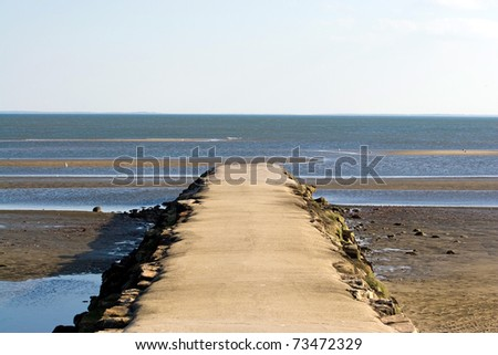 A jetty at the beach extends out into the ocean around low tide. - stock photo
