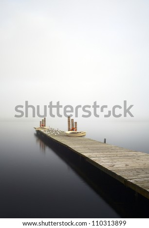 A jetty leading in to a fog covered Loch Lomond from Duckbay marina, Scotland.