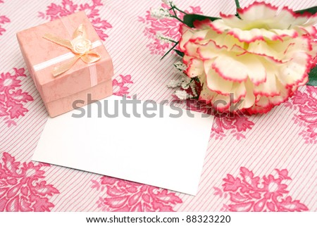 A jewelry box on top of a blank notecard. - stock photo