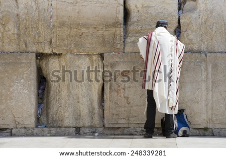 A jewish man is praying in front of the western wall in the old city of Jerusalem - stock photo