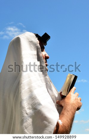A Jewish man wearing Tallit and Tefillin read from the Torah book pray to God under the sky on Jewish holiday. Religion Concept copy space - stock photo