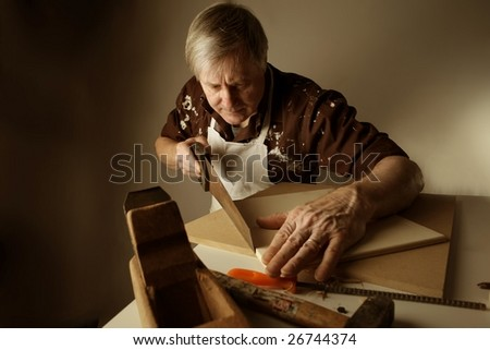 a joiner sawing a plank with an handsaw - stock photo