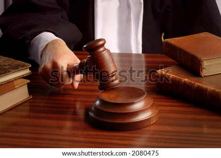 a judge hand striking a gavel over a table - stock photo