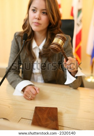 A judge in a courtroom striking the gavel (Focus on Gavel) - stock photo