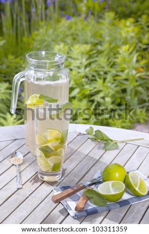 a jug and glass with non-alcoholic caipirinha,on a garden table. - stock photo