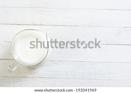 a jug of milk on white wooden table - stock photo