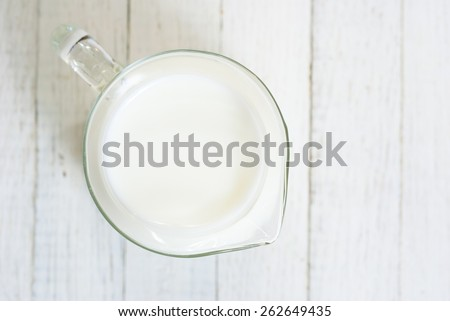 a jug of milk on wooden table - stock photo