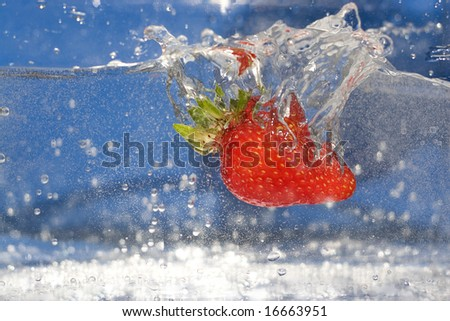 A juicy red strawberry plunging into some water. - stock photo