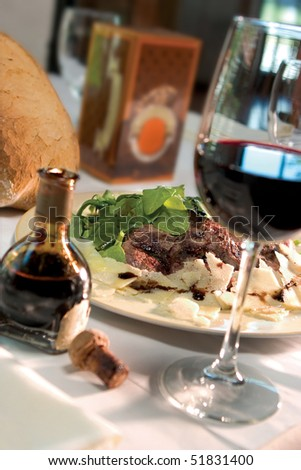 A juicy steak dinner garnished with fresh parmesan cheese and served with a glass of red wine.