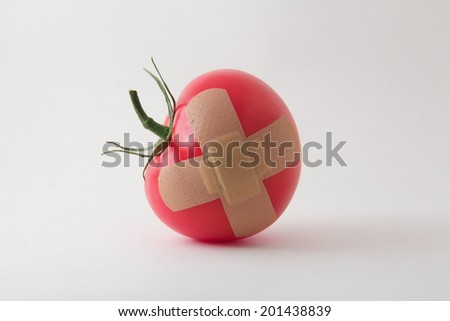 A juicy tomato with a bandage x - stock photo