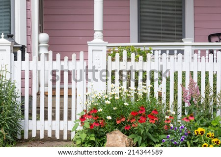 A jumble of daisies, red coneflowers, violas, astilbes, and yellow pansies at the gate to a pink Victorian home. - stock photo