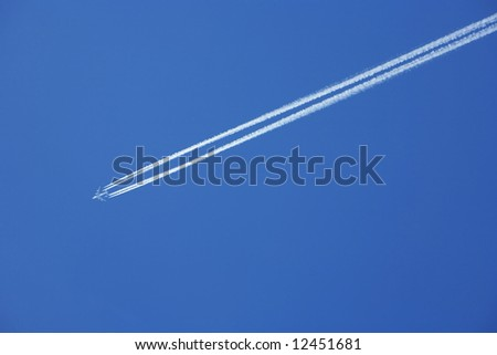 a jumbo jet flies across a blue sky leaving vapour trails - stock photo