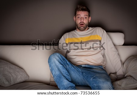 A jumpy man watching a scary movie - stock photo