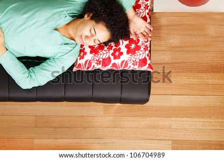 A jung brazilian woman sleeping on the sofa. - stock photo