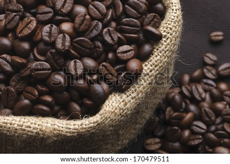 A juta bag with roasted coffee beans, on brown background  - stock photo