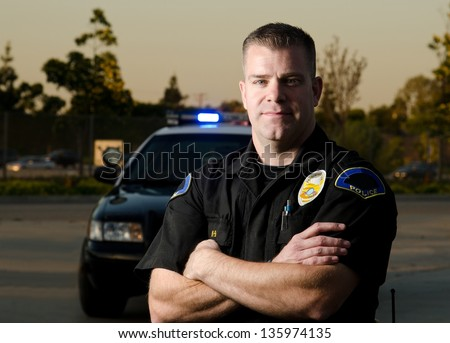 A K9 police officer standing in front of his patrol car with crossed arms. - stock photo