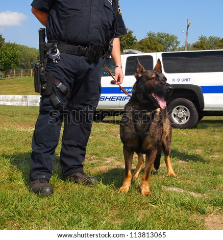 A K-9 unit police dog stands calmly next next to an armed law officer. - stock photo