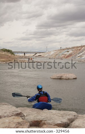 A kayaker gets ready to launch into the urban rapids created in the Arkansas River near downtown Pueblo, Co., taken in May, 2005. - stock photo