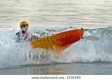 A kayaker paddles through the surf and nearly capsizes his kayak. - stock photo