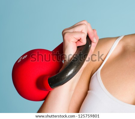 A kettlebell grip, woman's arm, blue background - stock photo