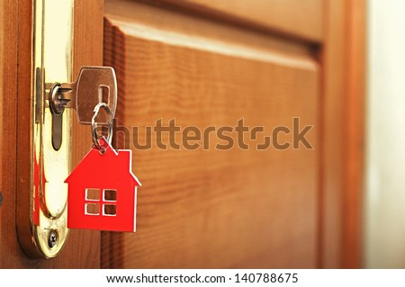 A key in a lock with house icon on i - stock photo