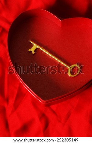 A key is placed inside a heart shaped box for the affection of loyalty. - stock photo