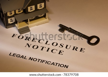 A key laying next to a house model and a foreclosure notice. - stock photo