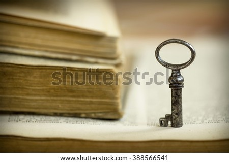 A key on an open old book - solution, wisdom concept - stock photo