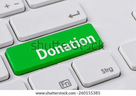 A keyboard with a green button - Donation